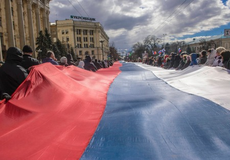 People carry a giant Russian flag during a pro-Russian rally in Kharkiv