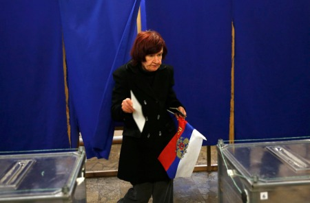 A woman holds a Russian flag as she prepares to cast her ballot during a referendum on the status of Ukraine's Crimea region at a polling station in Sevastopol