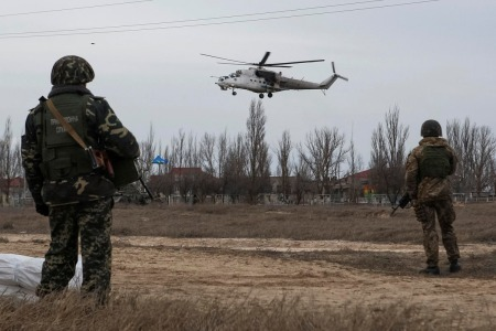 Ukrainian servicemen guard a checkpoint as a Ukrainian MI-24 military helicopter flies near the village of Strelkovo