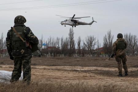Ukrainian servicemen guard a checkpoint as a Ukrainian MI-24 military helicopter flies near the village of Strelkovo