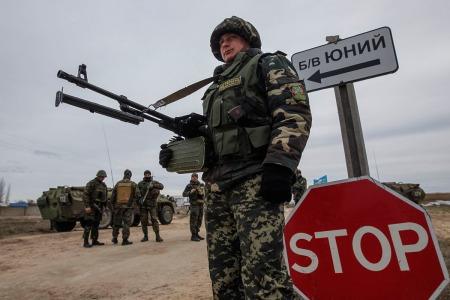 Ukrainian servicemen guard a checkpoint near the village of Strelkovo